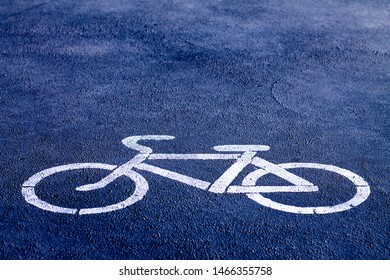 bicycle sign stencilled with white paint on a bright blue sidewalk indicating a designated area for cycling