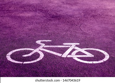 bicycle sign stencilled with white paint on a bright purple sidewalk indicating a designated area for cycling