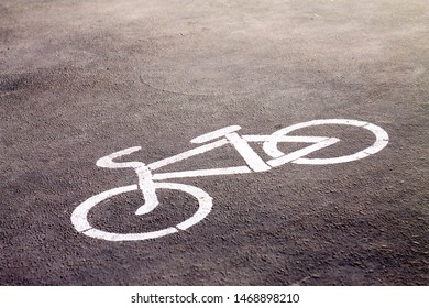 bicycle sign stencilled with white paint on a bright color sidewalk indicating a designated area for cycling