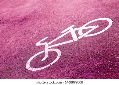 bicycle sign stencilled with white paint on a bright pink sidewalk indicating a designated area for cycling
