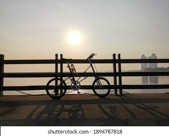 Bicycle silhouette beachside when sun goes down with cityskape backround