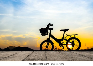 Bicycle silhouette with sun set wih wooden board.