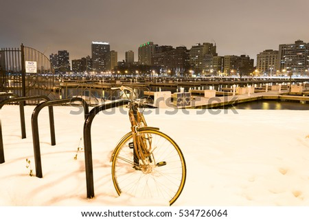 Bicycle in snow by a harbor