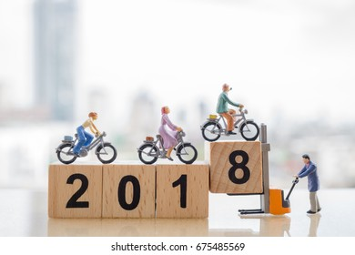 Bicycle sport and happy new year 2018  concept. Miniature people : Small figure friends cycling on 2018 wooden block and fork lift worker with modern city background.