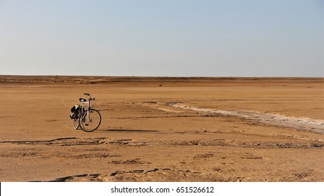 A bicycle stands alone in the Sahara desert.