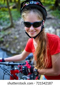 Bicycle teen with ladies bikes in autumn park. Womens road bike for running on nature. Teenager girl in helmet cycling fording throught water. Sunglasses for travelers.