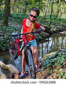 Bicycle teen with ladies bikes in summer park. Womens road bike for running on nature. Teenager girl in helmet cycling fording throught water . Cycling trip is good for health outdoor.