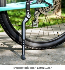 Bicycle telescopic kickstand close-up with rear bicycle wheel standing on the asphalt with green grass on the background in springtime