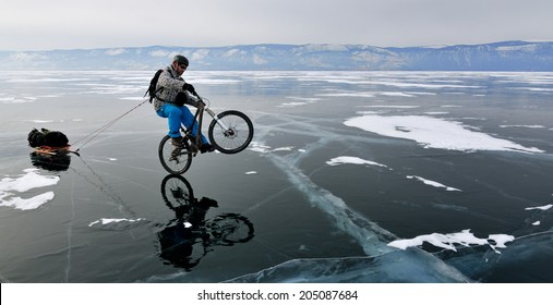 Bicycle tourist on the bike with sledge riding on the rear wheel only and having fun on the frozen lake