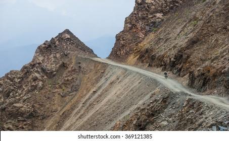 Bicycle tourist riding down the bumpy gravel mountain road