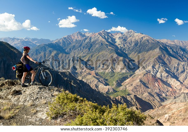 Bicycle traveler standing at cliff and enjoying mountain view