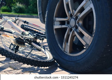 Bicycle under the wheel of a car. Dangerous cyclist driving. Car accident.