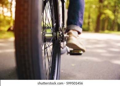 Bicycle wheel and men leg on pedal