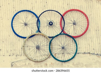 Bicycle wheels colored as the olympic circles, hanged on the outdoor wall