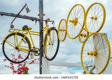 Bicycle and wheels hanging on a pole, with sky sun in the background, to indicate to cyclists the route to follow. Decorative bicycle hanging vintage photo background. Bicycle wheel rim against sky