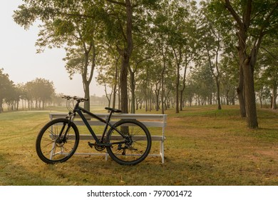 A bicycle with white bench having golf court as background