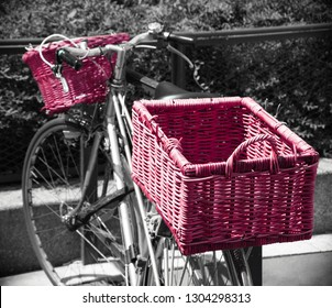 Bicycle with wicker baskets parked near park in Paris (France). fence Urban healthy lifestyle. Ecologic transport concept.  Retro toned pink black white photo. Vintage background.