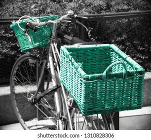 Bicycle with wicker baskets parked near park in Paris (France). fence Urban healthy lifestyle. Ecologic transport concept.  Retro toned green turquoise black white photo. Vintage background.