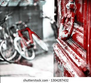 Bicycles in the backyard. View through the open antique wooden door. Paris, France. Parisian urban eco lifestyle. Selective focus on the handle and blurry background. Retro aged red black white photo