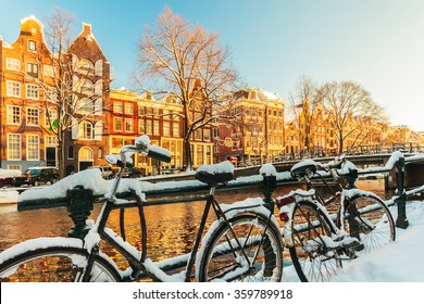 Bicycles covered with snow in front of a canal during winter in Amsterdam