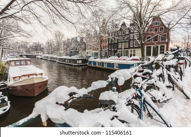 Bicycles covered with snow on a bridge during winter in Amsterdam