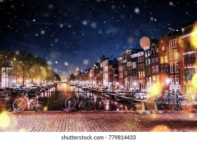 Bicycles Parked Along a Bridge Over the Canals of Amsterdam, Netherlands during a snowstorm. Bokeh light effect, soft filter. Night illumination of buildings and boats near the water in the canal.