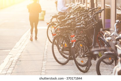 Bicycles parked along the road in Copenhagen. Photo taken at sunset with sunlight coming from top left. Many persons in Denmark use bike for commuting and moving around.