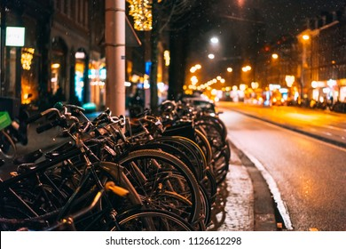 Bicycles parked along the road, night, falling snow