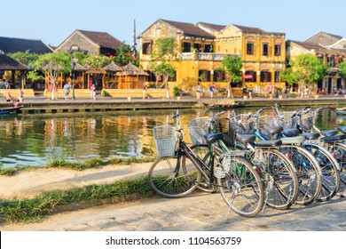Bicycles parked beside the Thu Bon River in Hoi An Ancient Town (Hoian), Vietnam. Traditional yellow buildings are visible in background. Hoi An is a popular tourist destination of Asia.