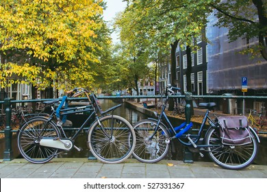 Bicycles parked on a bridge in Amsterdam, The Netherlands. Beautiful autumn view in Netherlands.