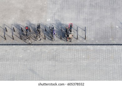 Bicycles parked on street chained to metal barriers. Top view