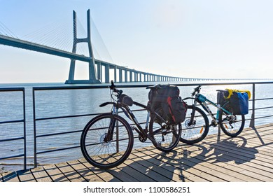 Bicycles prepared for travel. Morning, the beginning of the way. Vasco da Gama Bridge in Lisbon, Portugal.