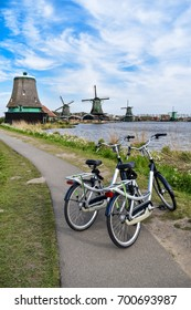Bicycles and traditional Dutch old wooden windmill in Zaanse Schans - museum village in Zaandam. Sign of Netherlands.