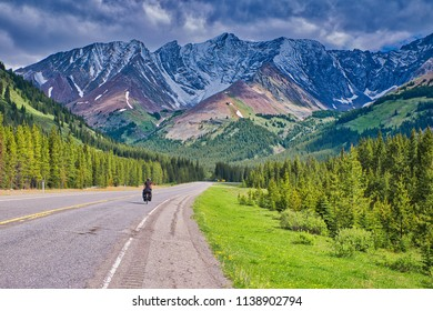 Bicyclist is climbing the mountains. A beautiful scenery with green trees and a endless road .