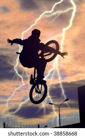 The bicyclist on a bicycle in a jump, on a background of the sky and flash lightning