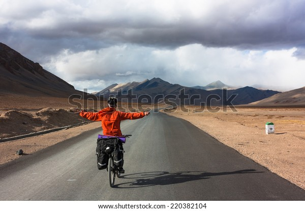 Bicyclist riding in storm fantastic landscape on mountain road, Jammu and Kashmir State, North India