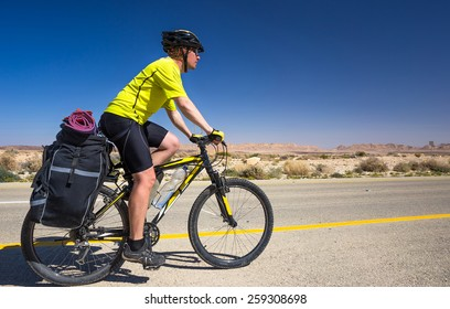Bicyclist in yellow T-shirt rides on the road