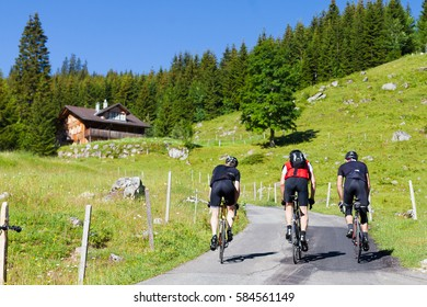 Bicyclists riding uphill on a steep Swiss Alps road. Background of green hills, trees, blue sky and chalet house.