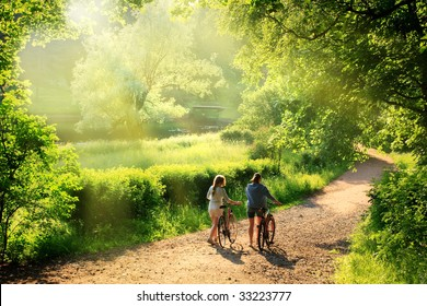 Bicyclists walk in the park with their bikes