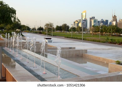 BIDDA PARK, Doha, Qatar - March 21, 2018: View of fountains in the newly opened Bidda Park in the centre of Qatar's capital, with distant city skyine.