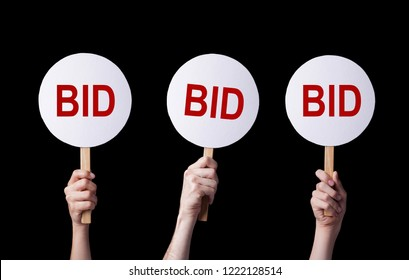 Bidders' hands lifting auction paddles