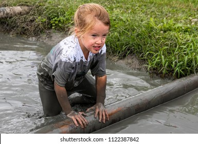 Biddinghuizen, The Netherlands - June 23, 2018: Child during a mudrun (mudraise) in the mud and in the water climbing a tree trunk.