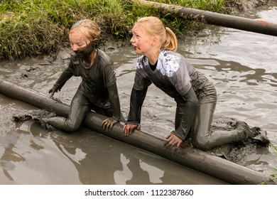 Biddinghuizen, The Netherlands - June 23, 2018: Children, girls, during a mudrun (mudraise) in the mud and in the water climbing a tree trunk.