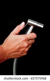 bidet shower in hand  isolated on black background