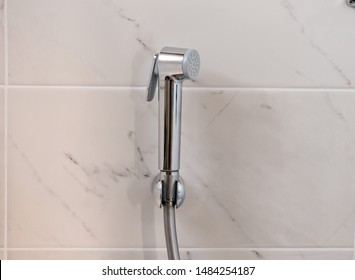 Bidet shower on the wall. Close-up.