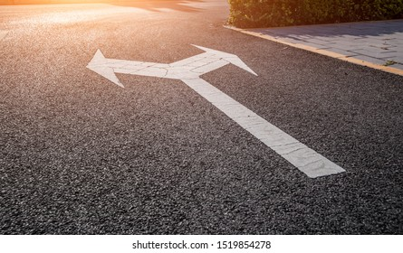 A bi-directional arrow symbol on a wet asphalt road for the concept of choice at a junction.