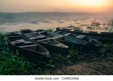 Biebrza Natural Park - foggy sunrise over Biebrza river.  Fishing boats on the shore.
