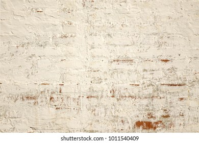 Biege and Gray Dirty Plaster Wall, With Falling Off Flakes Of Paint. Rough Surface. Old Weathered Painted Background Texture. Vintage Timber Background. Peeled Plaster Brickwall