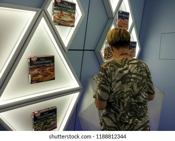 BIELEFELD, NORTH RHIJN WESTFALEN / GERMANY – JULY 8 2015: Female visitor looking at wall with pizza boxes by Dr. Oetker World.