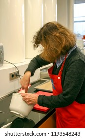 BIELEFELD, NORTH RHIJN WESTFALEN / GERMANY – NOVEMBER 6 2015: Woman with red apron at work in kitchen by Dr. Oetker World.